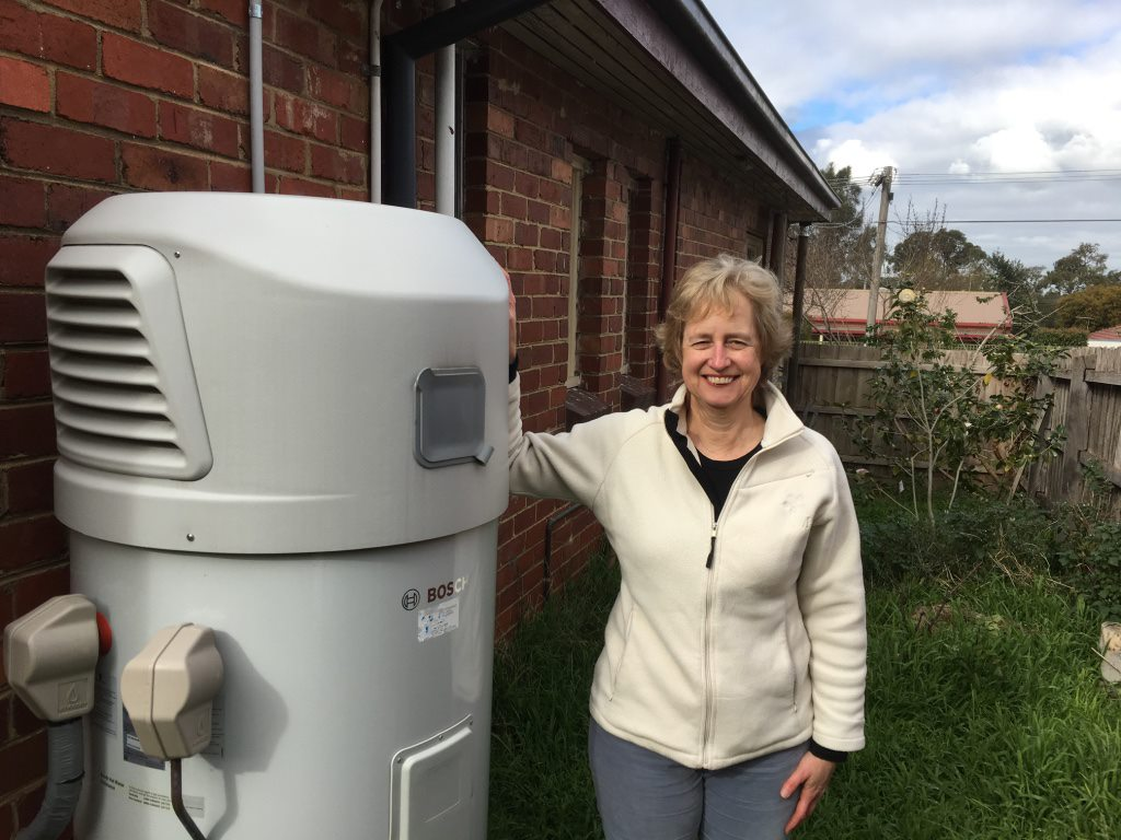Jane Fisher with a heat pump she installed